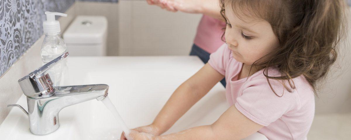 Menina a lavar as mãos