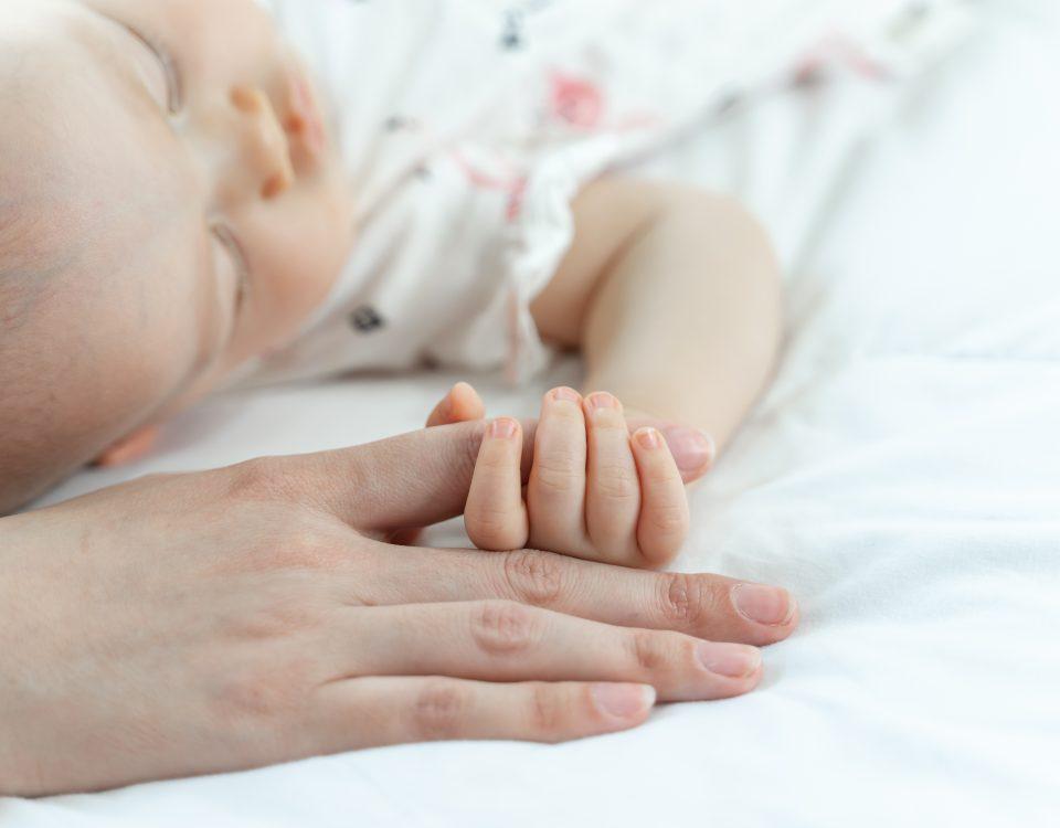 Bebé a agarrar a mão da mãe