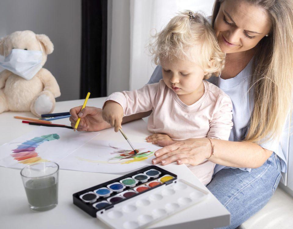 Criança a desenhar com a mãe